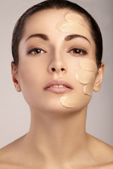 Young woman with cosmetic foundation on a skin.
