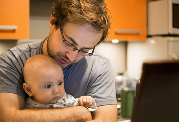 Father with baby in front of laptop