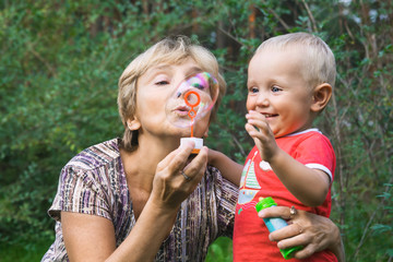 Grandmother and  kid with soap bubbles