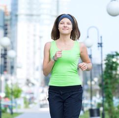 Woman jogging in city street park.
