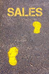 Yellow footsteps on sidewalk towards Sales message