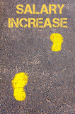 Yellow footsteps on sidewalk towards Salary Increase message poster