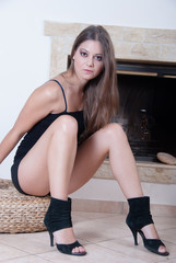 Attractive young woman near the fireplace
