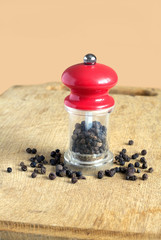 Peppercorn and manual mill with red cap on wooden board