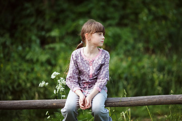 Little girl sitting on a wooden fence