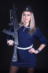 Woman in a navy uniform with an assault rifle