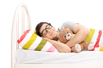 Childish young man sleeping with a teddy bear