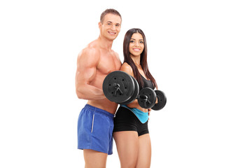Couple of young athletes exercising with barbells