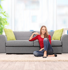 Relaxed young woman sitting by a sofa
