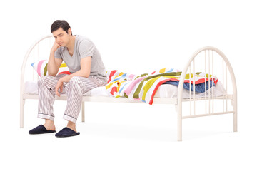 Worried guy sitting on a wooden bed