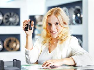 Female customer with car key in a showroom