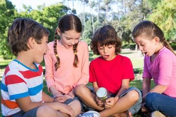 Happy little friends looking at jar