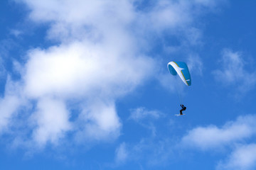 Paragliding in the blue sky with skis