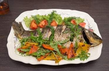 The baked carp with vegetables and spices