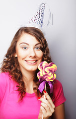 Funny curly woman  holding big lollipop.