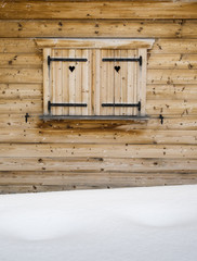 wooden shutters on a cabin window with snowdrift  in forground