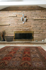 Masonry wall and brass fireplace in living room