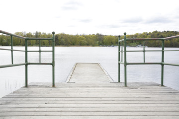 Wood pier with iron railing by lake, Stockholm, Sweden.