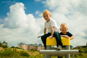 Children in playground kids boys playing on leisure equipment