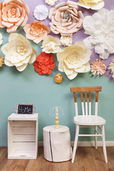 Handmade furniture on paper flowers background at home.