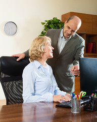 office scene with two mature and happy workers