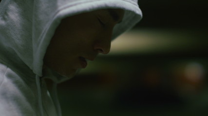 Hooded male breathing heavy after a workout in slow motion