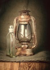 Rusty  lamp and a bottle of kerosene