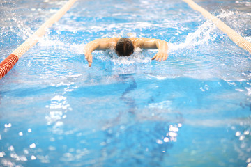 Adult training butterfly stroke technique in the pool
