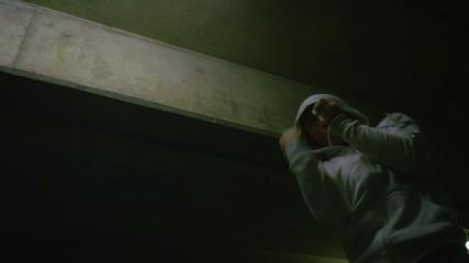 Hooded man doing boxing training in urban setting