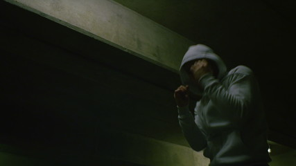 Hooded male boxer training at night alone in slow motion