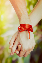 Man's and woman's hands tied with ribbon