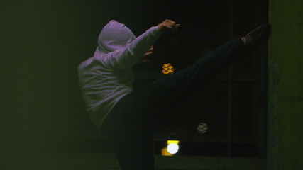 Hooded male fighter training at night in urban setting