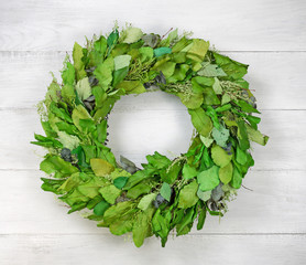 Seasonal green leaf wreath on rustic white wood