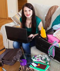 Happy brunette woman choosing ticket online