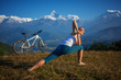 woman practicing yoga, relaxing after riding bikes high in mount - 79202444