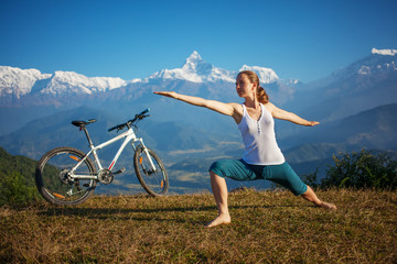 woman practicing yoga, relaxing after riding bikes high in mount