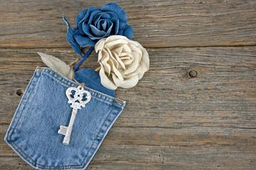 denim roses in blue jean pocket with old key