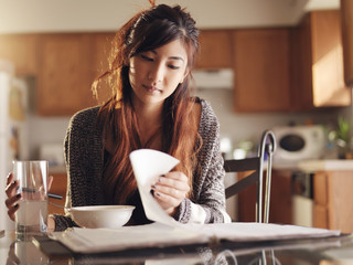 teen asian girl studying in kitchen