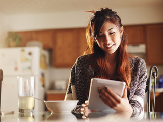 asian teen girl using tablet at breakfast