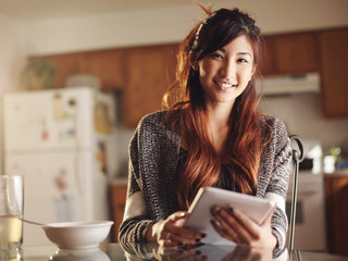 asian teen using tablet at breakfast portrait