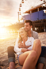 couple sitting in the sand on the beach near santa monica pier