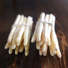 two bunches of white asparagus on wooden table