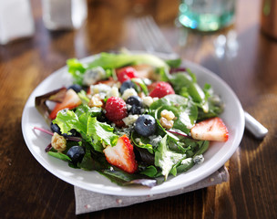 tasty mixed berry salad with blue cheese crumbles and walnuts
