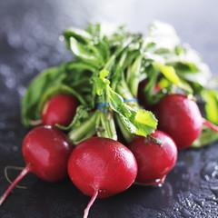 bunch of fresh radishes on slate surface