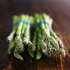 two bunches of asparagus on wooden table top