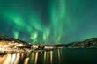 Northern Lights over village in Norway coast