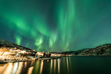 Northern Lights over village in Norway coast