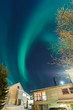 Aurora Borealis above suburbs and house in Norway