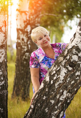Smiling senior woman holding tree trunk in park