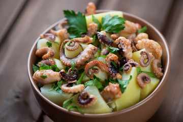 Octopus salad with potato and parsley, selective focus